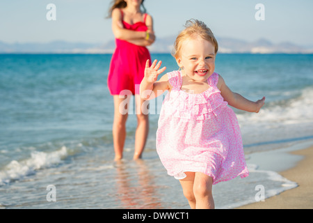 Little girl running on the beach - Stock Photo