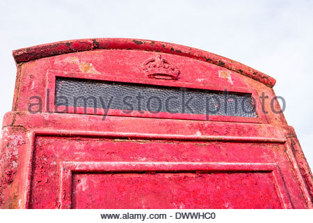 Old and weathered red telephone kiosk - Stock Photo