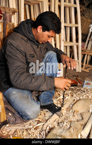 Woodworker in workshop drilling hole with hand auger bit in wood for chair part, Marrakech, Morocco, North Africa - Stock Photo