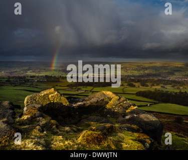 Intense dramatic rainbow over rural Yorkshire village, Burley-in-Wharfedale, UK - Stock Photo