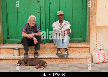Two old Cuban men with a dog sitting on doorstep, Trinidad, Cuba - Stock Photo