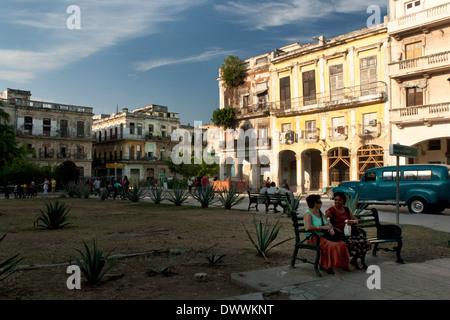People sitting and talking on benches in a park in Plaza del Cristo Cuba, La Habana Vieja, Havana, Cuba - Stock Photo