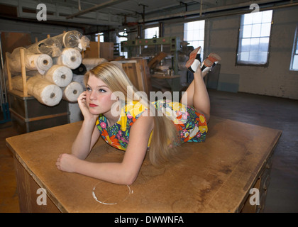 A 16-year old girl wearing a 1950's flowered dress and black and white saddle shoes sits on a desk in a corset factory - Stock Photo