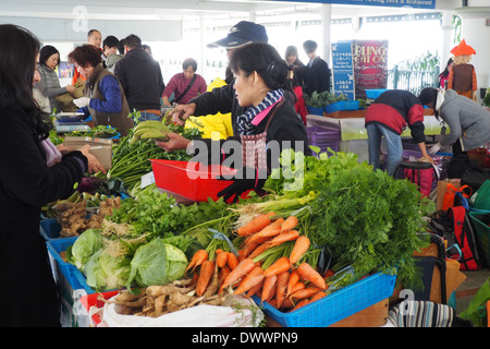 Sunday markets set up in the Star Ferry terminal on Hong Kong Island selling fresh fruit and vegetables. - Stock Photo
