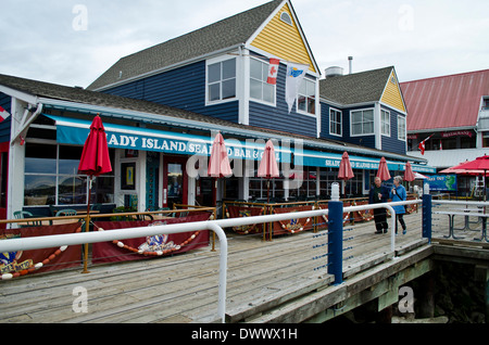 Couple strolling along the boardwalk by the water in Steveston, a historic fishing village near Richmond British - Stock Photo
