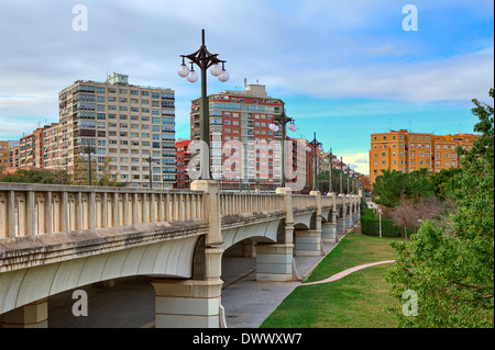Bridge across old river bed of Turia towards contemporary residential buildings in Valencia, Spain. - Stock Photo