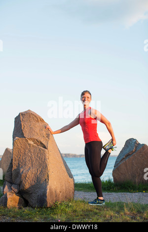 Full length of woman doing stretching exercise by rock at seaside - Stock Photo