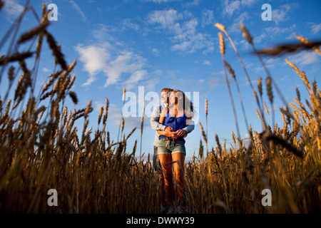 Affectionate young couple embracing while standing on wheat field - Stock Photo