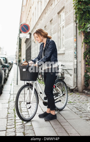 Mid adult woman searching for something into bag in bicycle basket at street - Stock Photo