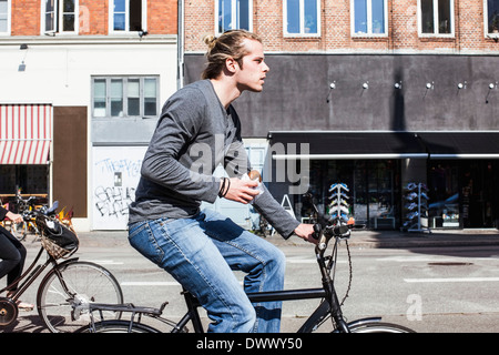 Profile shot of young man holding burger while riding bicycle on city street - Stock Photo