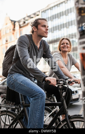 Man and woman cycling on city street - Stock Photo