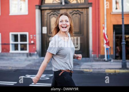 Portrait of happy mid adult woman walking on city street - Stock Photo