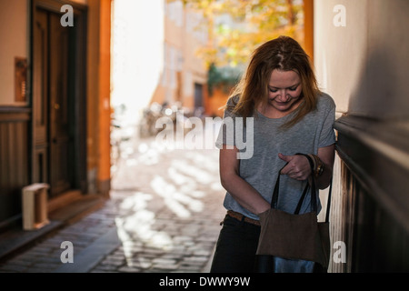 Mid adult woman searching something into purse - Stock Photo