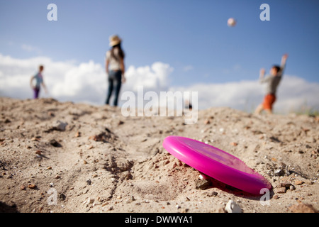 Plastic disc on sand with people playing in background - Stock Photo