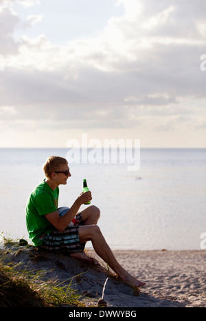 Full length of young man holding beer bottle at beach - Stock Photo