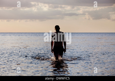 Rear view of man walking in sea - Stock Photo