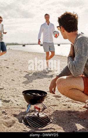 Young man with barbeque grill looking at friends on beach - Stock Photo