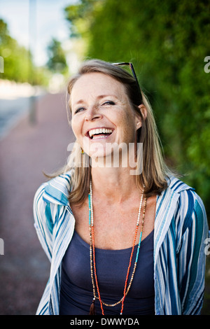 Portrait of woman laughing outdoors - Stock Photo