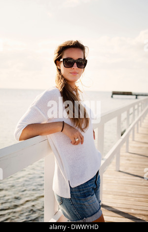 Portrait of beautiful young woman in sunglasses standing on pier - Stock Photo