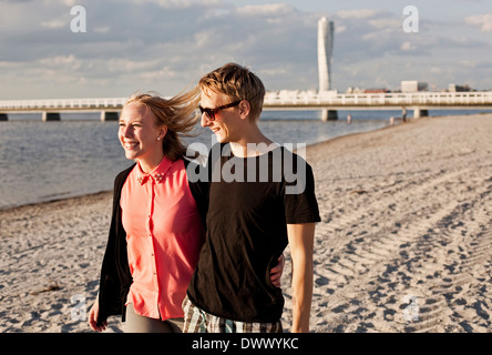 Happy young couple walking on beach - Stock Photo