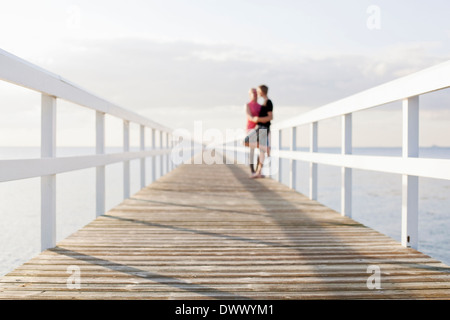 Couple standing on pier - Stock Photo