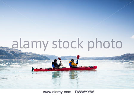 People kayaking on sea against clear sky - Stock Photo