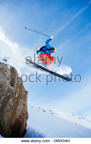 Low angle view of mid adult man skiing against sky - Stock Photo