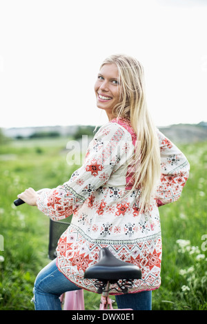 Rear view portrait of young woman standing with bicycle on field - Stock Photo