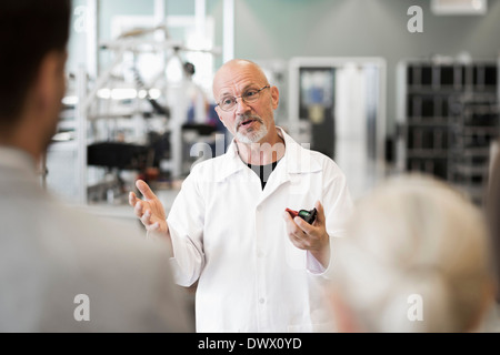 Male engineer discussing with business people in manufacturing plant - Stock Photo