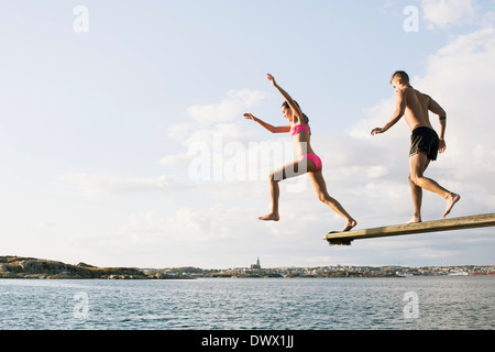 Full length of young couple diving into lake against cloudy sky - Stock Photo
