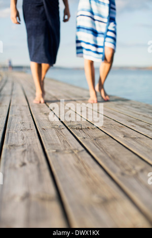 Low section of couple wrapped in towels walking on wooden pier - Stock Photo