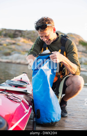Happy man searching something in bag by kayak - Stock Photo