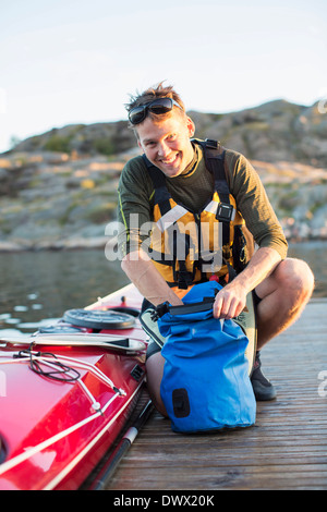 Portrait of happy man searching something in bag by kayak on pier - Stock Photo
