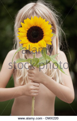 Shirtless girl holding sunflower in front of face outdoors - Stock Photo