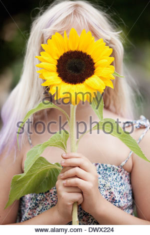 Girl holding sunflower in front of face outdoors - Stock Photo