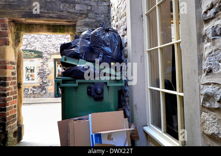 A wheelie bin with bin bags piled on top in an alley way Bakewell Derbyshire England uk - Stock Photo