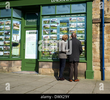 A middle aged couple looking at an estate agents window bakewell Derbyshire England uk - Stock Photo