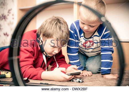 Siblings playing video game at home - Stock Photo