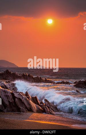 Sunrise view of waves crashing onto the rocks at Slapton Sands, Devon, UK - Stock Photo