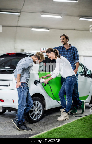 Male friends with woman charging electric car at gas station - Stock Photo