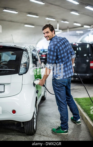 Full length portrait of young man charging electric car at gas station - Stock Photo