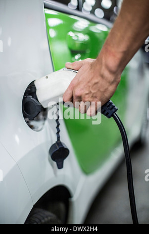 Cropped image of man charging electric car at gas station - Stock Photo