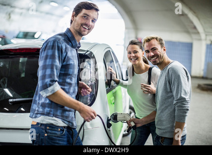 Portrait of happy friends with man charging electric car at gas station - Stock Photo