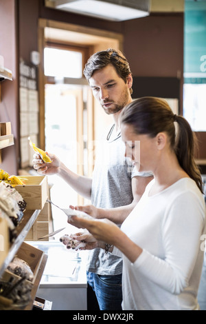 Side view of friends reading label in supermarket - Stock Photo
