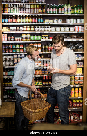 Young male friends reading label against shelf in supermarket - Stock Photo