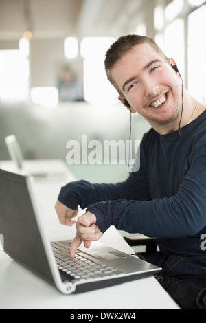 Portrait of happy businessman with cerebral palsy using laptop while listening music - Stock Photo
