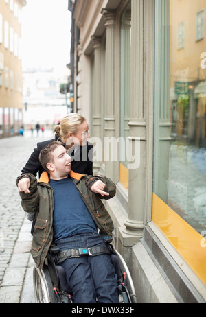 Disabled man on wheelchair widow shopping with caretaker - Stock Photo