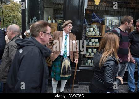 An onlooker in a kilt smoking a cigarette on the Royal Mile before the start of a pro-Independence march in Edinburgh, - Stock Photo