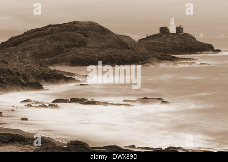 Mumbles Head and Lighthouse shrouded in spray sepia tone in Swansea Bay, site of proposed tidal Lagoon. The light - Stock Photo