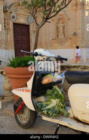 Old motor scooter with some groceries outside the Church of the Visitation in Gharb. Gozo Island. Malta - Stock Photo
